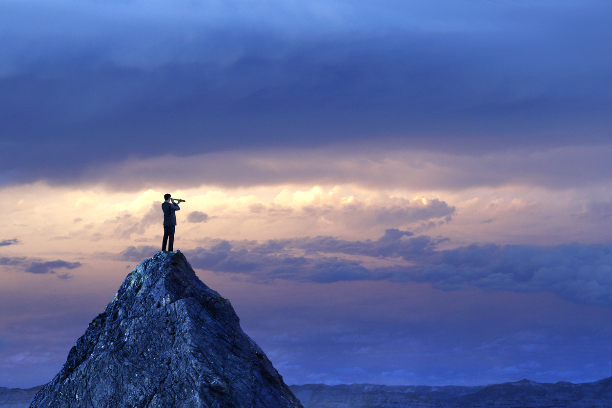 man standing on a mountain looking through a spyglass